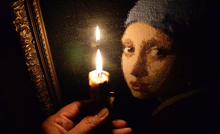 Горящая свеча на фоне вышитой крестиком картины в одной из квартир во Владивостоке.