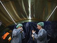 22 апреля 2020. Врач и медсестра надевают защитные костюмы в мобильном госпитале для больных коронавирусом в Стокгольме, Швеция
