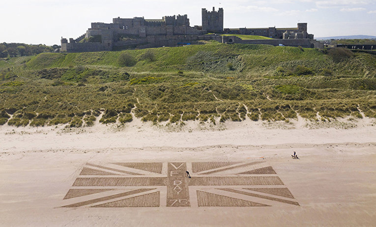 Изображение флага на пляже у замка Бамбург в Великобритании