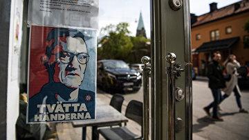 10 мая 2020. Портрет главного эпидемиолога Швеции с призывом мыть руки на двери работающего ресторана, Стокгольм, Швеция