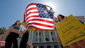 Участники акции протеста против самоизоляции в Сакраменто, штат Калифорния, США