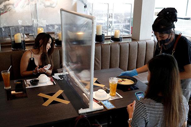 Посетители обедают во вновь открывшемся ресторане в Бангкоке