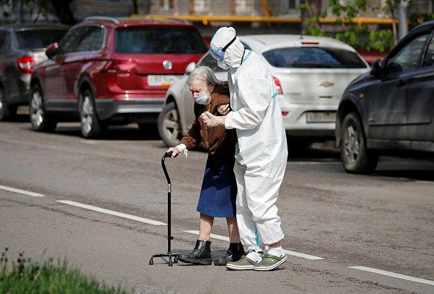 Медицинский работник помогает пожилой женщине перейти дорогу в Москве