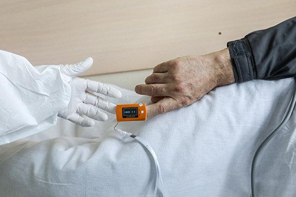 Медицинский работник проверяет пульсоксиметр у пациента с коронавирусом в ЦКБ «РЖД-Медицина» в Москве
