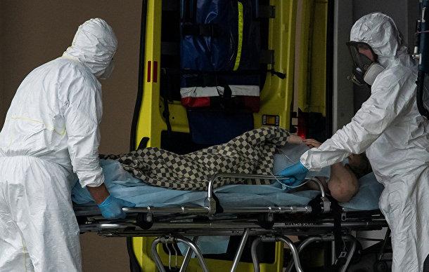 Медицинские работники перевозят больного коронавирусом на окраине Москвы