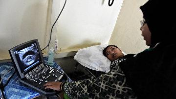 Врач делает УЗИ беременной женщине в медицинской клинике в Шукадане, Индонезия