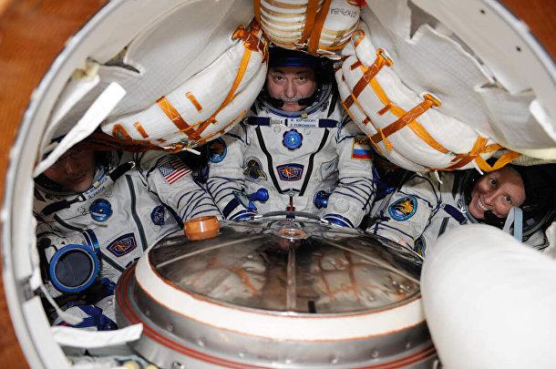Два астронавта и космонавт внутри спускаемого модуля «Союз» в 2010 году