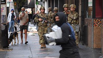 Мародер с коробками пробегает мимо солдат национальной гвардии США в Голливуде