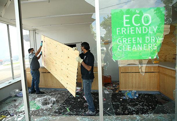 Рабочие устанавливают фанеру в разбитые витрины магазина в Миннеаполисе