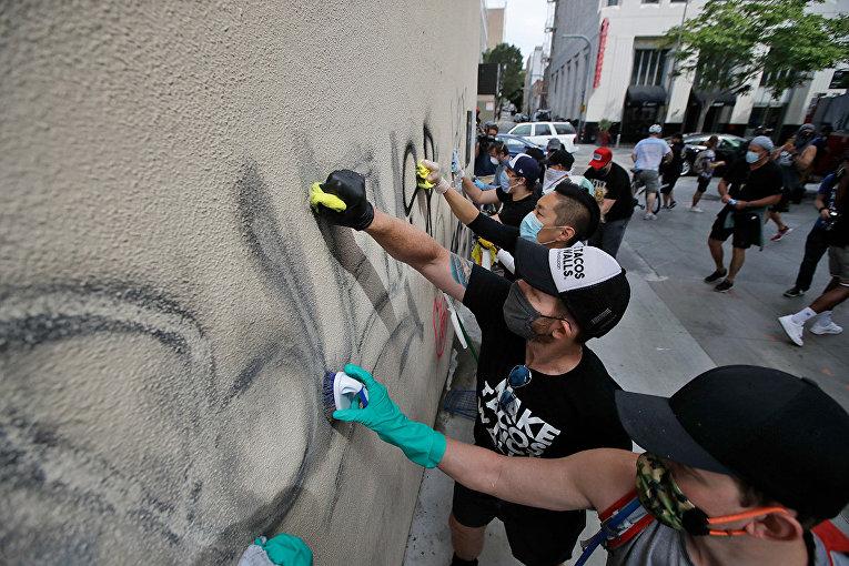 Волонтеры смывают граффити со стены магазина в Санта-Монике