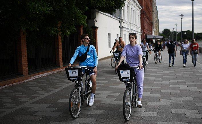 Люди катаются на велосипедах по Берсеневской набережной в Москве