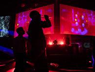 Диджей и посетители в ночном клубе в Берлине, Германия