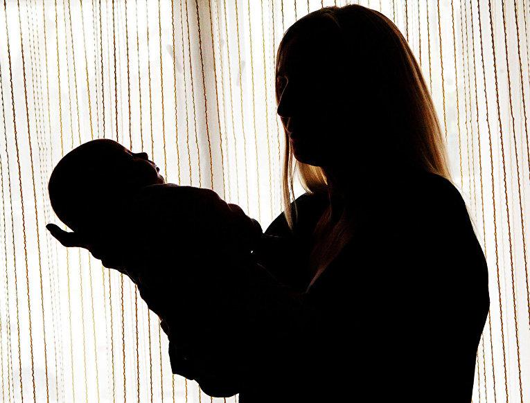 Женщина держит на руках ребенка, родившегося от украинской суррогатной матери в городе Ужгороде