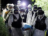 Сотрудники полиции несут тело мэра Сеула Пак Вон Суна