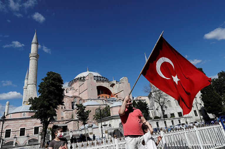 10 июля 2020. Мужчина с флагом Турции рядом с Собором Святой Софии в Стамбуле