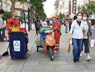 Ослабление карантинных мер в Китае. Прохожие на улице в Пекине
