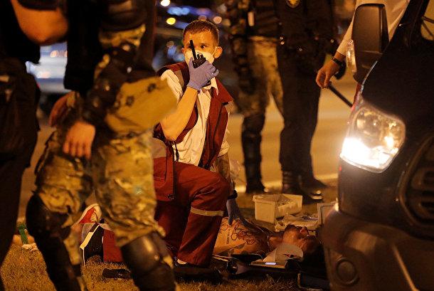 Медик оказывает помощь раненому во время акции протеста в Минске