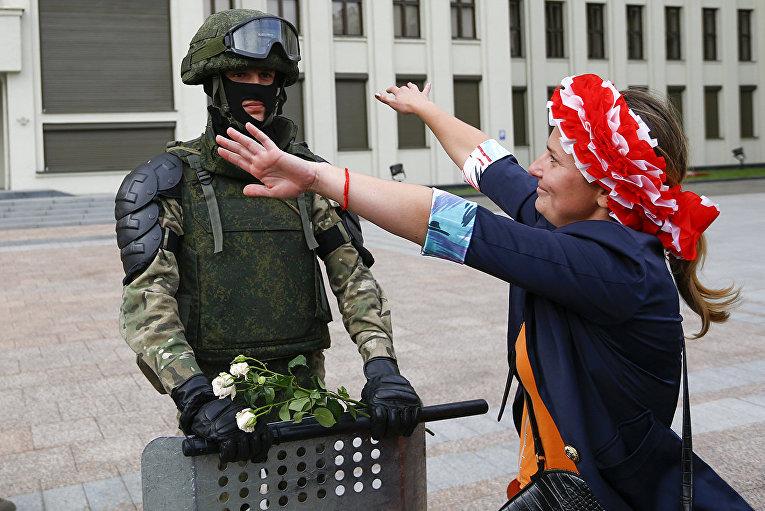 Женщина обнимает солдата, охраняющего здание белорусского правительства в Минске