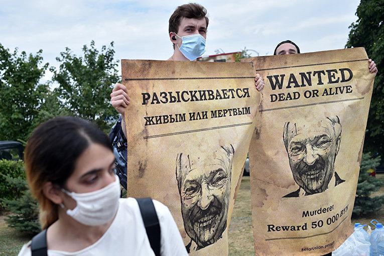Люди с плакатами, изображающими президента Белоруссии Александра Лукашенко во время акции протеста в Минске