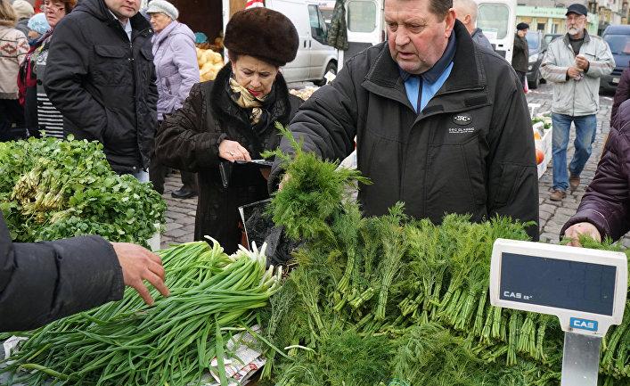 Покупатель приобретает укроп на ярмарке местных сельхозпроизводителей в Калининграде