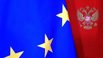 Флаг Евросоюза на фоне стены с гербом РФ