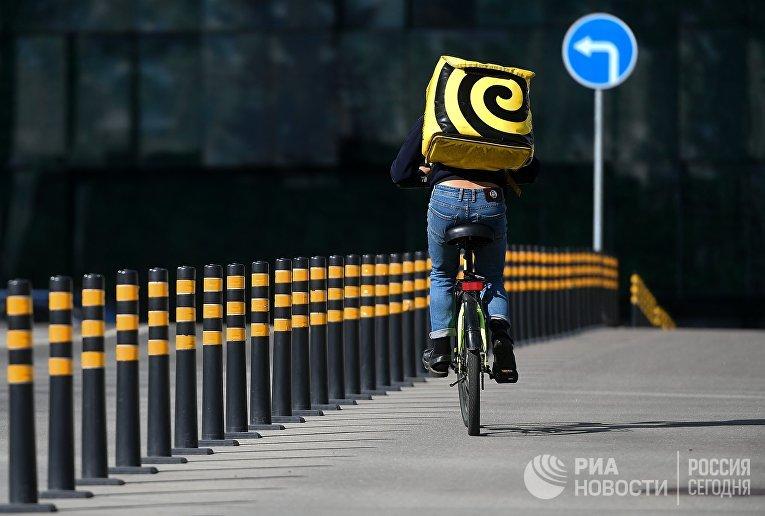 """Курьеры службы доставки """"Яндекс.Еда"""" на одной из улиц в в Москве"""