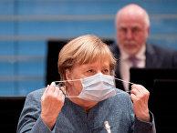 Канцлер Германии Ангела Меркель надевает защитную маску