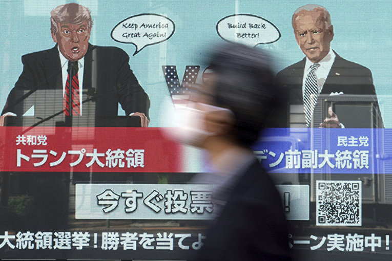 Дональд Трамп и Джо Байден на экране в Токио