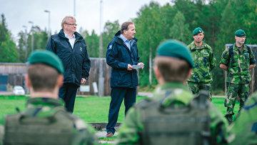 Министр обороны Швеции Петер Хультквист и премьер-министр Стефан Лёвен во время визита на базу ВМФ