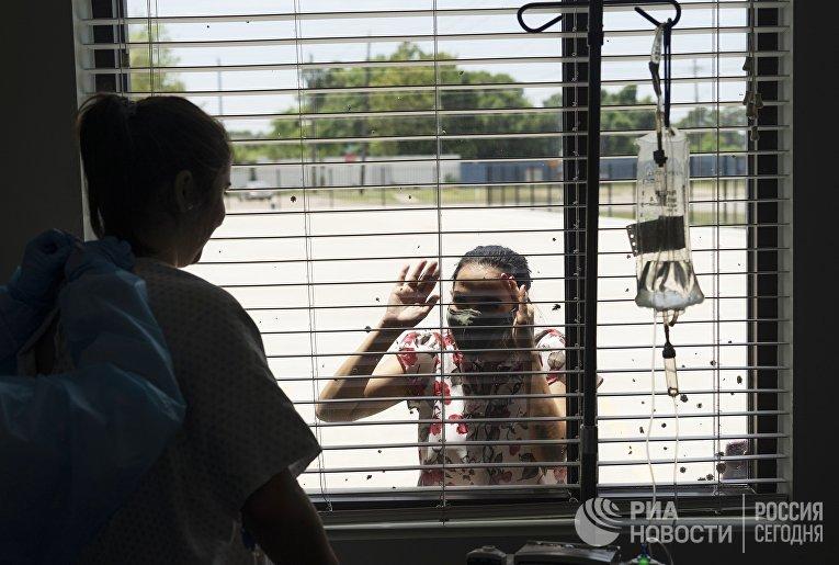 Пациентка общается через стекло с родственниками в госпитале United Memorial Medical Center в Хьюстоне, где проходят лечение больные с covid-19