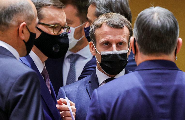 Президент Франции Эммануэль Макрон беседует во время встречи на саммите ЕС в Брюсселе, Бельгия