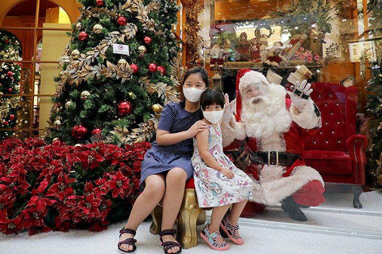 Санта-Клаус за защитным щитом в торговом центре в Куала-Лумпуре