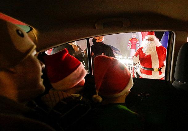 Дети приветствуют Санта-Клауса из автомобиля в Сьюдад-Хуаресе, Мексика