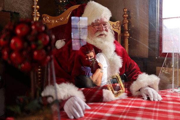 Санта-Клаус за защитным стеклом в торговом центре в Коммерсе, Калифорния