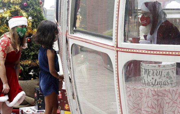 Девочка общается с Санта-Клаусом в Рио-де-Жанейро