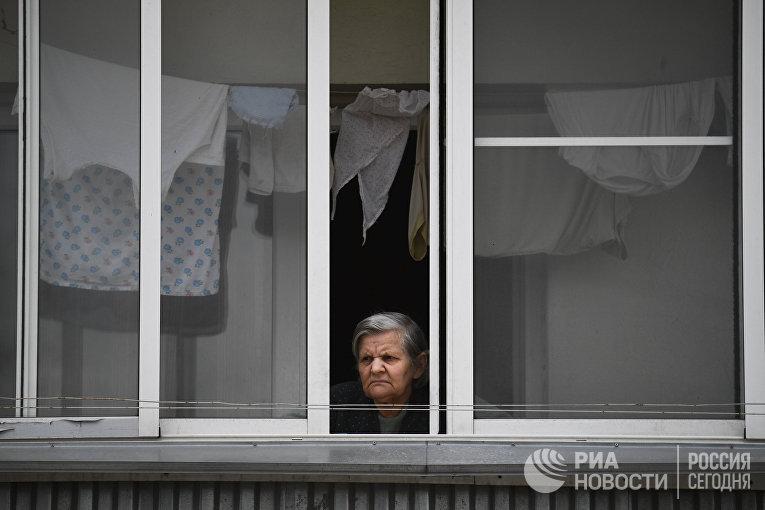 Женщина на балконе жилого дома