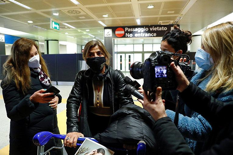 Представители СМИ беседуют с пассажирами из Великобритании в аэропорту Фьюмичино