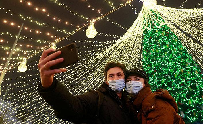 Пара делает селфи перед рождественской елкой в центре Киева