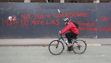 Велосипедист проезжает мимо забора со словами протеста против локдауна в Манчестере, Великобритания