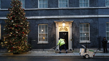 Уборщик подметает перед дверью резиденции премьер-министра Великобритании на Даунинг-стрит, 10, Лондон