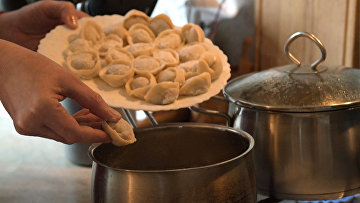 Женщина готовит пельмени