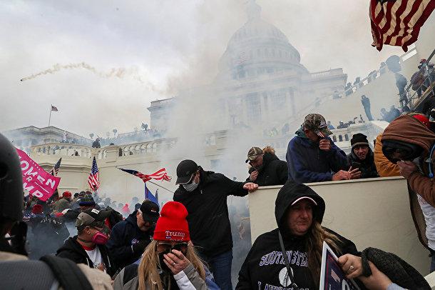 Сторонники президента США Дональда Трампа во время столкновения с полицией зданием Капитолия США в Вашингтоне