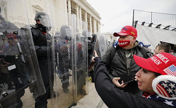 Сотрудники полиции и участники акции протеста сторонников действующего президента США Дональда Трампа у здания конгресса в Вашингтоне
