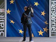 Журналист у входа в здание Европейской комиссии в Брюсселе