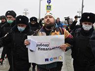 Сотрудники правоохранительных органов задерживают участника несанкционированной акции сторонников Алексея Навального в Москве