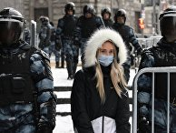 Жительница Москвы идет по Пушечной улице, огороженной сотрудниками правоохранительных органов перед началом несанкционированной акции сторонников Алексея Навального