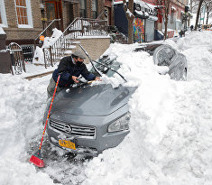 Мужчина отчищает автомобиль от снега в Нью-Йорке