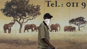 Местный житель в маске в Альбертоне, ЮАР