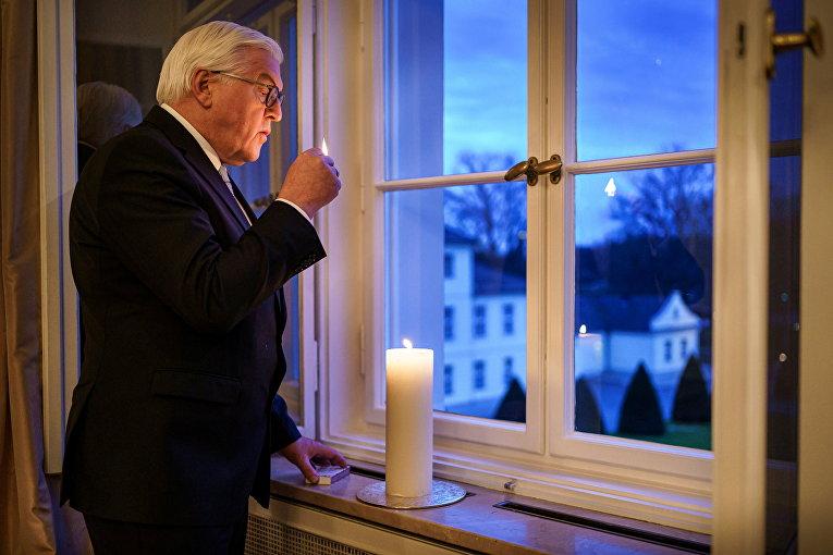 Федеральный президент ФРГ Франк-Вальтер Штайнмайер зажигает свечу в память о жертвах пандемии коронавируса