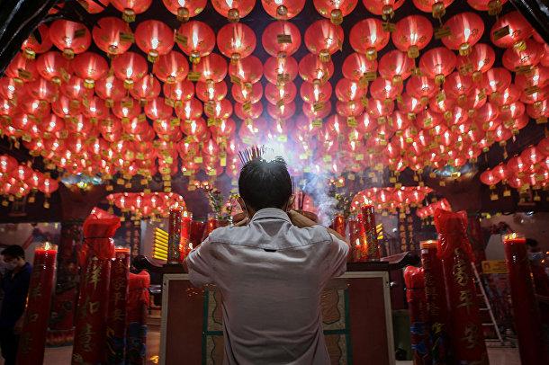 Верующий молится в канун Лунного Нового года в храме в Джакарте